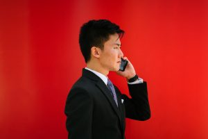 A man in a suit, making a phone call to find long distance movers Canada