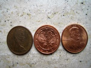 Three pennies on a grey surface.