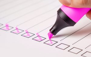 A pink marker making checklists.