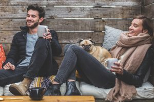 A man and a woman with a pug. They're relaxing, possibly reconnecting and solving expat problems of loneliness?