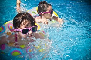 Two little girls with sunglasses swimming with swimming rings