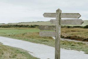 A wodden pedestal signage near a road