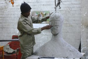 A man sculpting a big bust