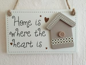 Board with cartoon house and words 'home is where the heart is'