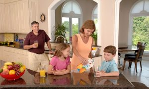 Family drinking juice in their suburban home.