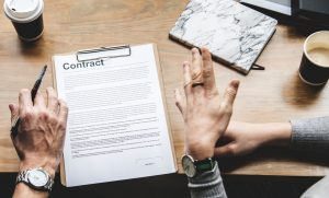 Two people talking about a contract in front of them