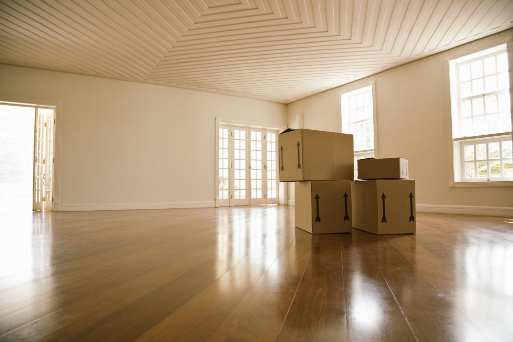 Moving boxes in empty room, representing residential movers Hamilton Ontario