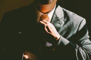 A man in a suit adjusting his tie