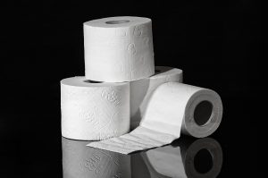 Four rolls of toilet paper on a black surface