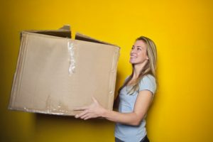Girl holding a cardboard box in front of a yellow background