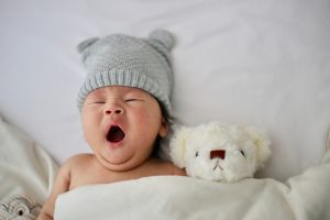 baby with a gray cap yawning in bed