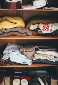 clothes folded on shelves for storing out-of-season clothing