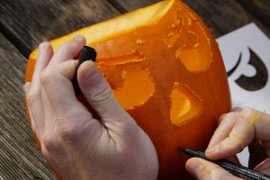 a man carving his pumpkin