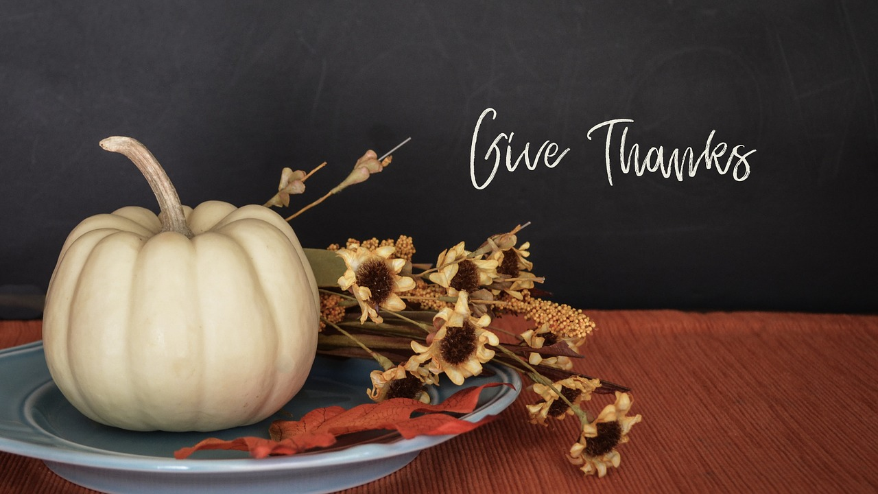 Give thanks in Hamilton this Thanksgiving with words on a black background and a pumpkin