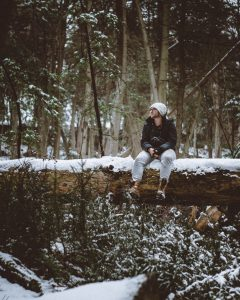 man wearing white cap sitting on a snowed in log thinking of things to do in Hamilton this winter
