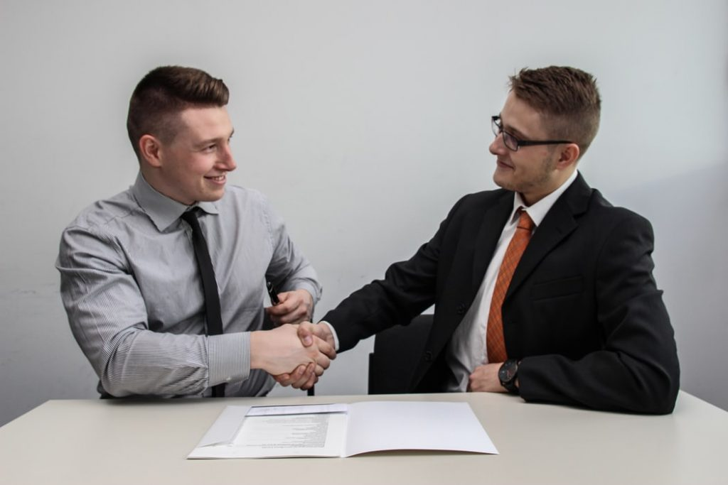 Two men shaking hands over a contract.