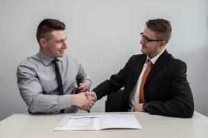 two gentlemen in suits shaking hands