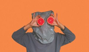 Man with grapefruit instead of eyes and a garbage bag over his head