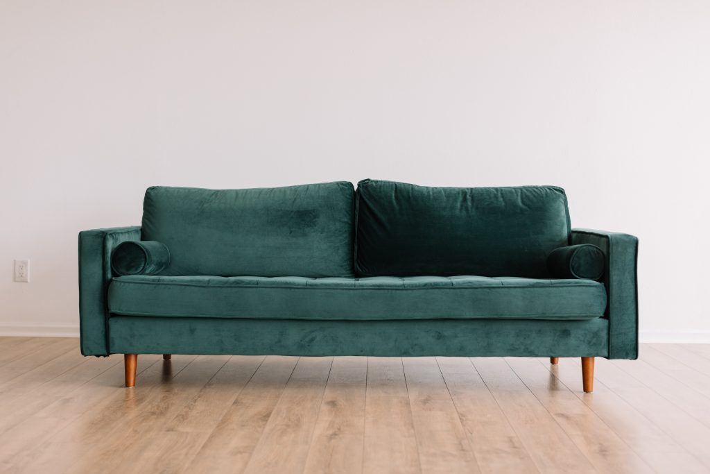 green couch on a wooden floor