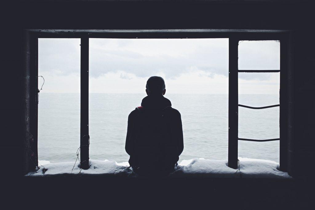 a man sitting on a window ledge