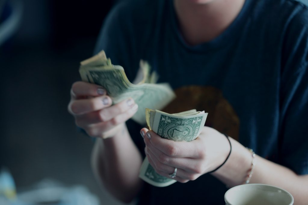 woman counting her money for moving to Toronto alone