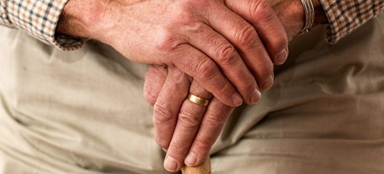 An old person's hands on a cane