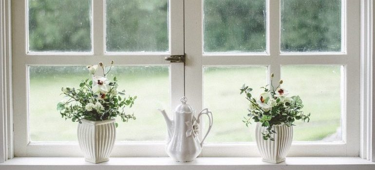 Residential moving services: a white window frame with white plant pots and tea kettle