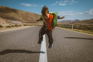 kid jumping on the road
