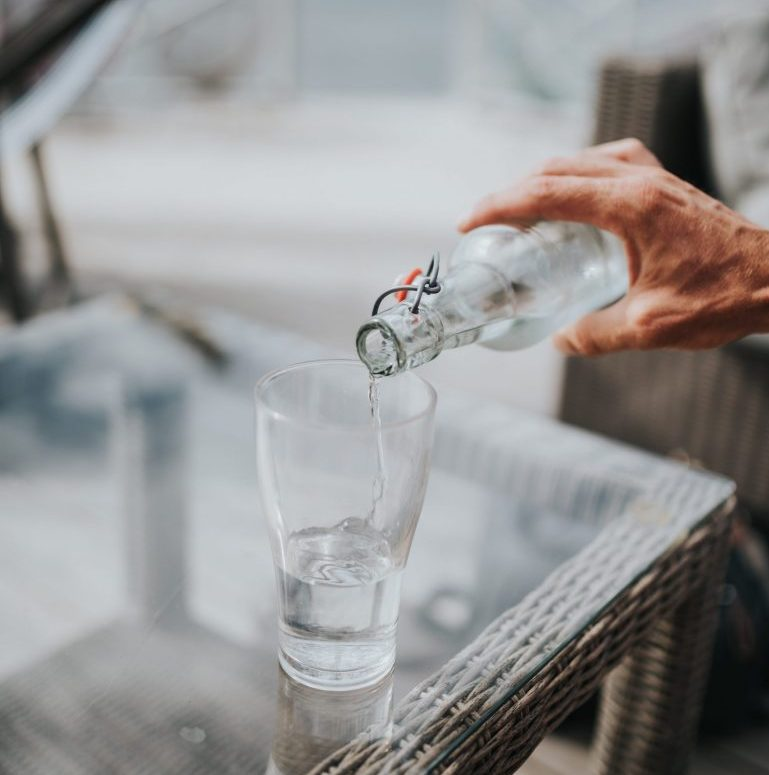 person pouring water into a glass