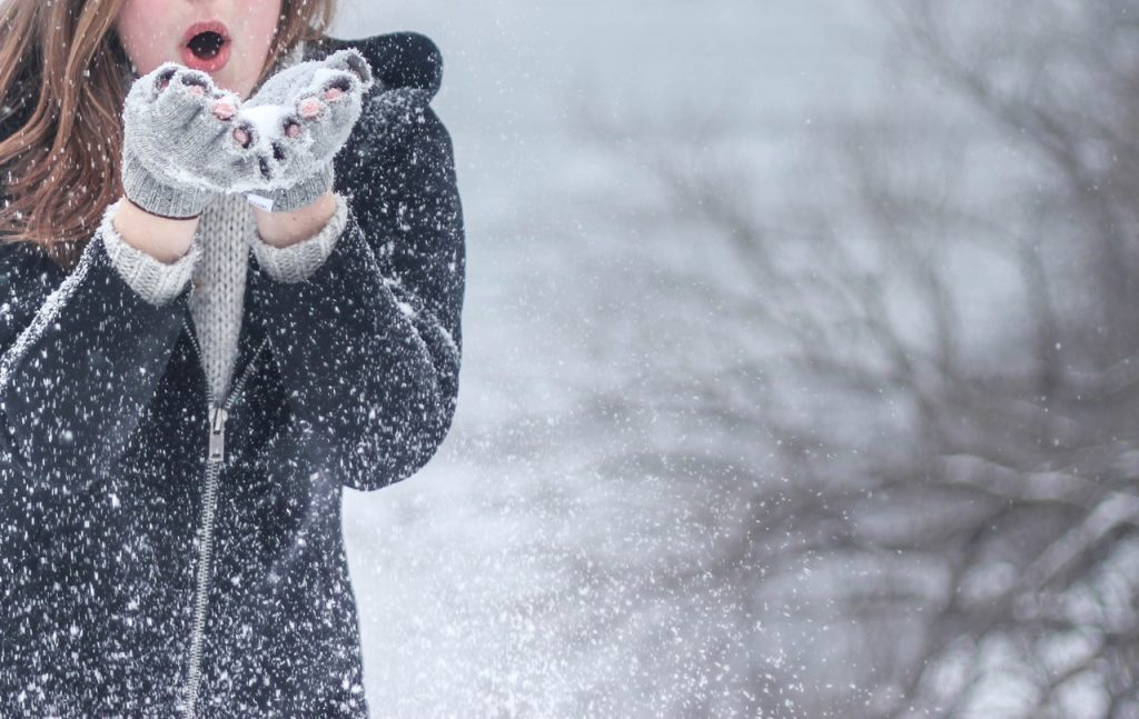 A woman blowing snow out of her hands