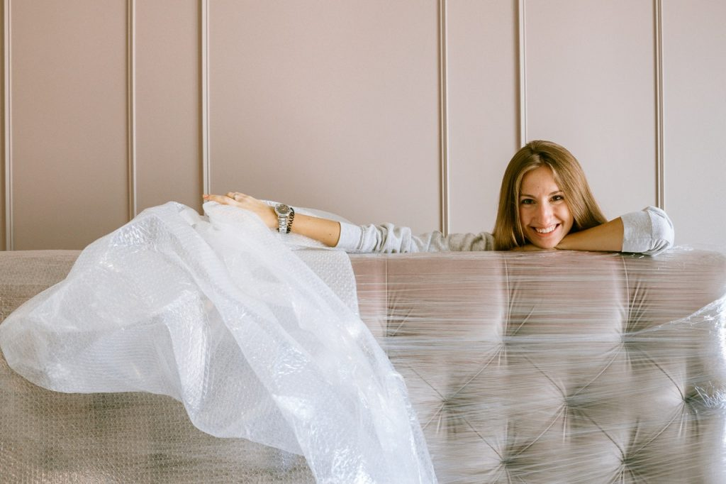 A woman wrapping a couch - one of the reasons to hire furniture movers in Toronto is for the safety of your furniture