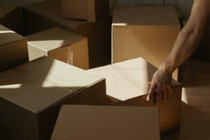 hand and a cardboard boxes
