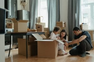 family playing with a child in a room with cardboard boxes