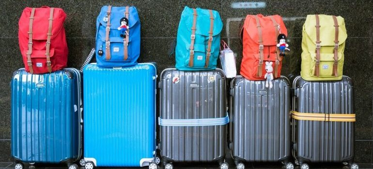 Colorful rucksacks on suitcases.