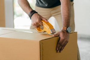professional mover taping a carboard box