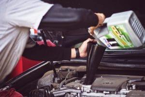 a car mechanic refilling the motor