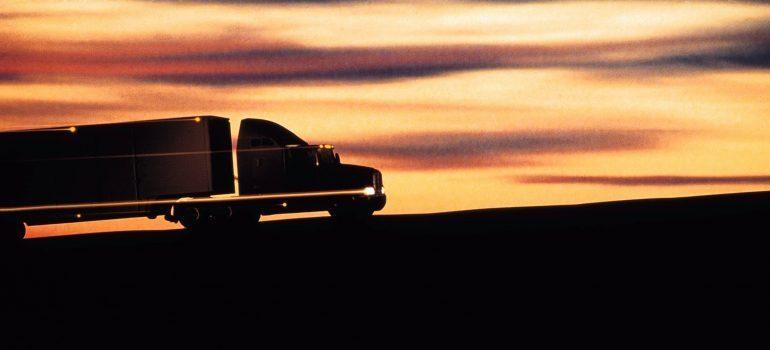 Silhouette of semi-truck driving