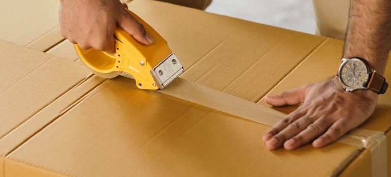 Man sealing box with tape