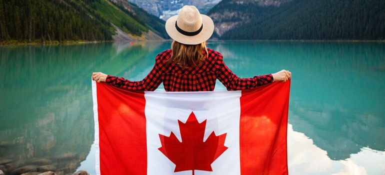 Woman holding flag of Canada in front of lake