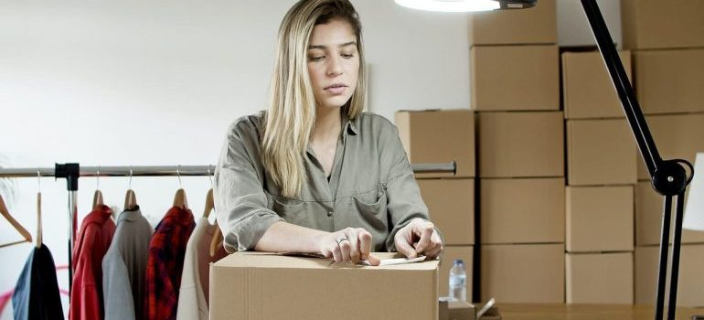 A woman packing moving boxes.