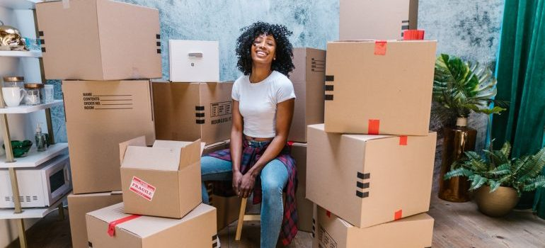 A woman sitting among the moving boxes and smiling.