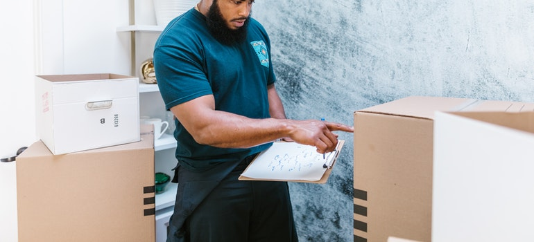 Moving company employee packing boxes