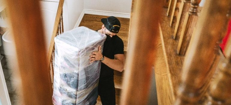 One of the best long distance movers Canada has carries a wrapped piece of furniture down the stairs