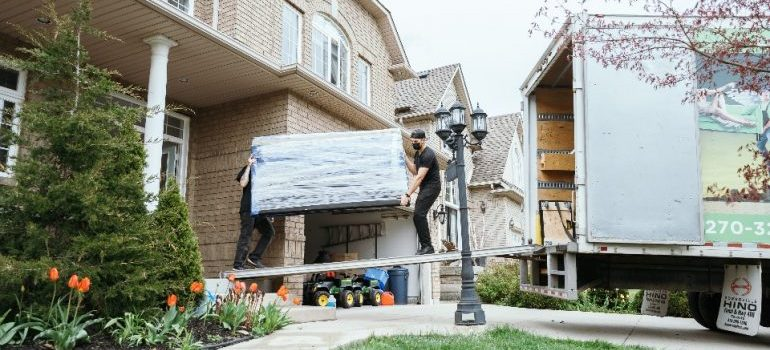 Number 1 Movers loading a sofa into the moving truck