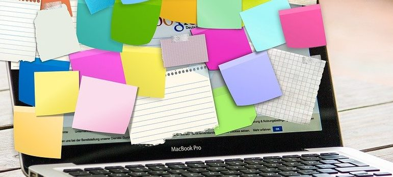 A laptop covered in sticky notes