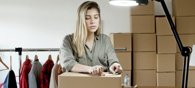a woman packing an item in a reusable box as a way to handle office waste disposal when moving