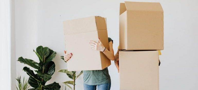 Two persons holding moving boxes