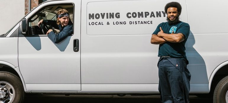 Mover standing next to a moving truck