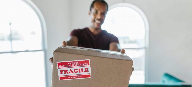 A mover holding a cardboard box