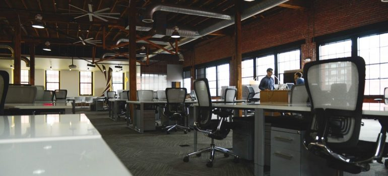 a half empty office with two employees inside it